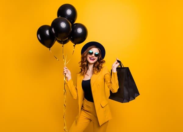 Frau mit Ballons und Einkaufstaschen