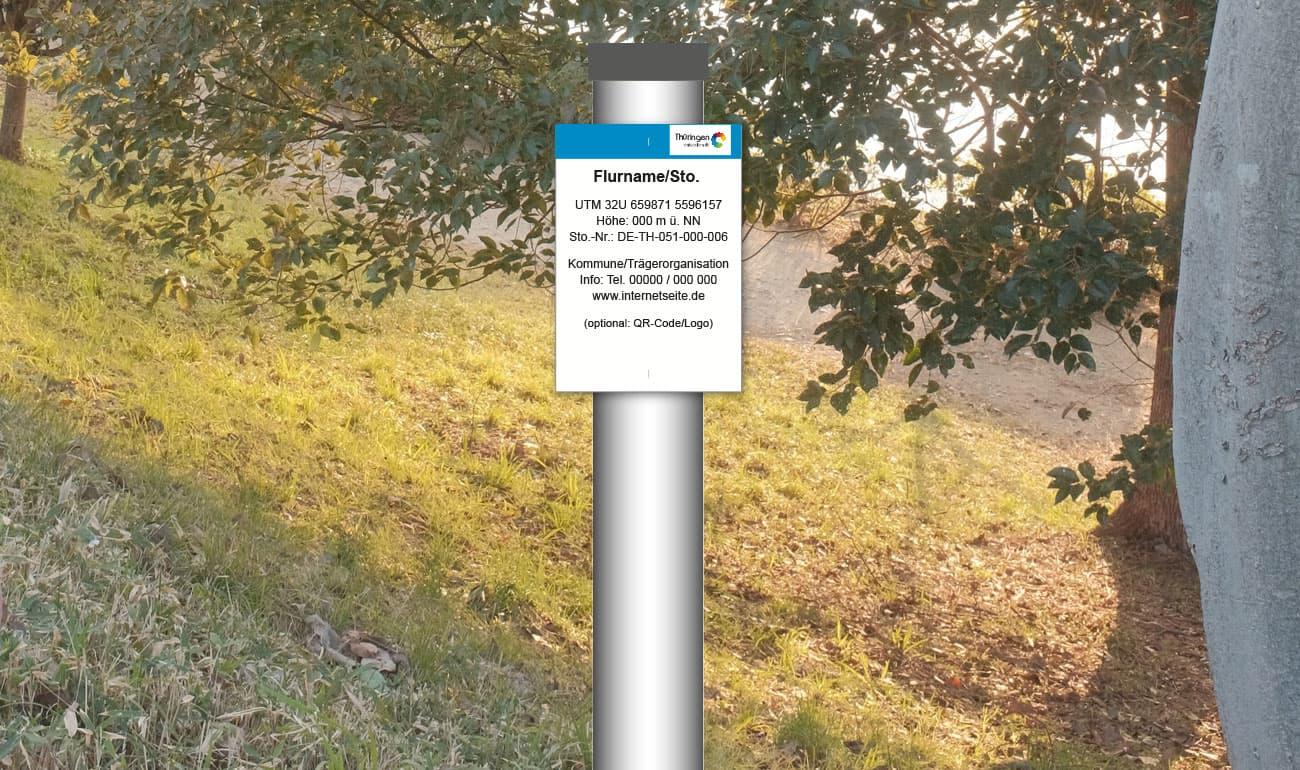 weißes Schild am oberen Rand ein blauer Balken mit Wald im Hintergrund