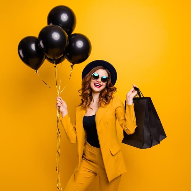 Frau mit Luftballons  und Einkaufstaschen
