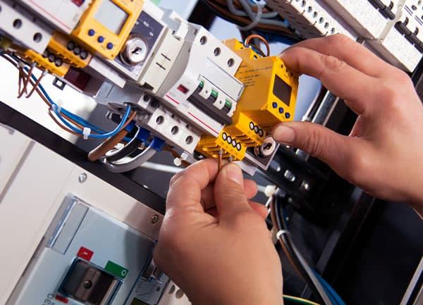 Hände arbeiten an elektrischen Bauteilen